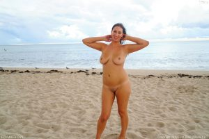 Thick horny MILF Tiffany parades fully nude on the beach showing her shaved pussy
