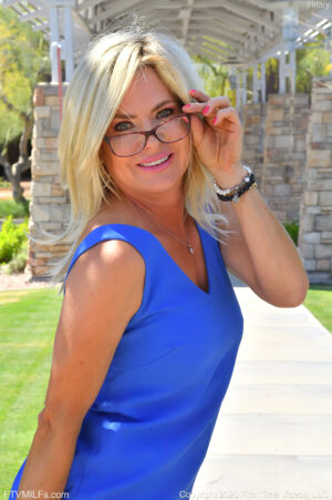 Blonde MILF in glasses Hilary modeling her short blue dress before fucking her dildo